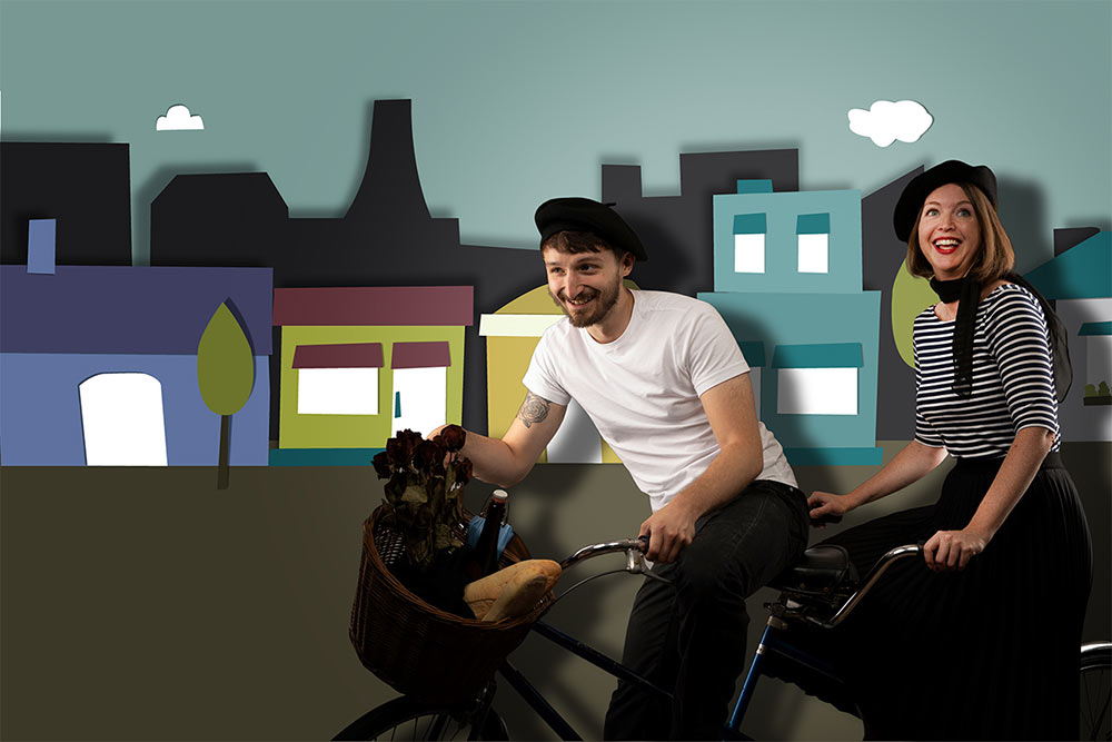 Two people on tandem bike on paper background of city:1 Day Website Licensing: Collaboration