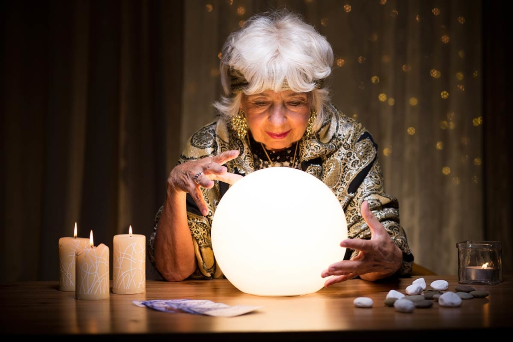Woman using crystal ball to predict web design trends for 2021